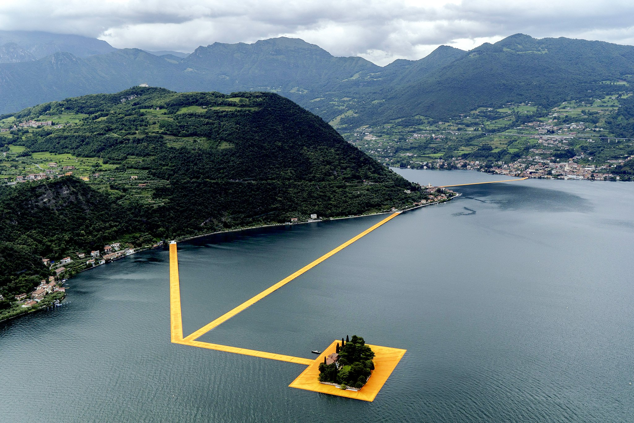 "Stretching For Nearly Two Miles, ""The Floating Piers"" Project By Artist Christo, That Connects Two Small Islands In Lake Iseo In Pilzone, Italy, June 16, 2016. ""The Floating Piers"" Is His First Outdoor Installation Since 2005, When He And Jeanne-Claude, His Collaborator And Wife, Who Passed Away In 2009, Installed 7,500 Golden-paneled Gates In Central Park In New York City. (Alessandro Grassani/The New York Times)"